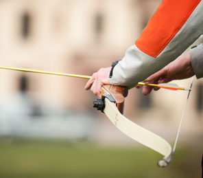 man with bow and arrow archery activities in Aldourie Castle Estate grounds