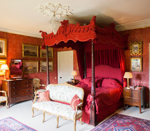luxury red bedroom with four-poster | Aldourie Castle Loch Ness | Luxury Exclusive Venues Scotland